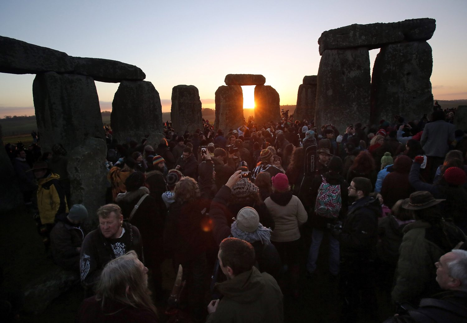 Matt Cardy/Getty Images.AMESBURY, ENGLAND - DECEMBER 21: People gather to watch the sunrise as druids, pagans and revellers celebrate the winter solstice at Stonehenge on December 21, 2012 in Wiltshire, England. Predictions that the world will end today as it marks the end of a 5,125-year-long cycle in the ancient Maya calendar, encouraged a larger than normal crowd to gather at the famous historic stone circle to celebrate the sunrise closest to the Winter Solstice, the shortest day of the year.